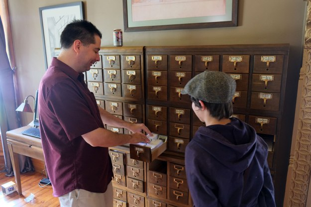 Aaron shows some of their stamp collection to Greta.